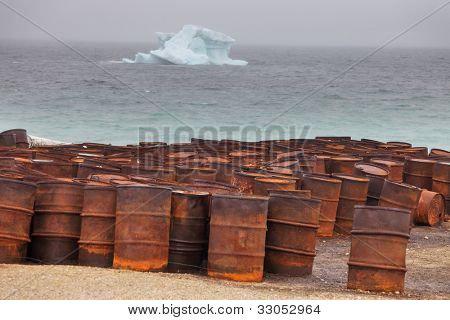 Rusty fuel and chemical drums on Arctic coast with iceberg on background
