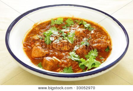 A Moroccan chicken tagine cooked with tomatoes, nuts, dates and spices, garnished with coriander leaves and almond slices