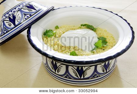 A north African pottery tagine bowl full of couscous, topped with fresh yoghurt and garnished with coriander leaves