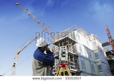 geodesy engineer, building site and mobile cranes