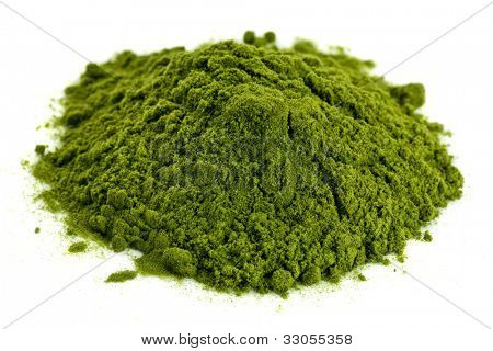 a small pile of green freeze-dried organic wheat grass powder, nutritional supplement