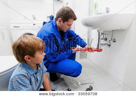 un fontanero reparar un lavabo roto en el baño
