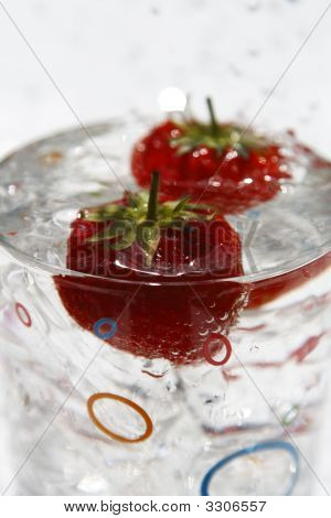 Water Glass Ice Cube And Strawberries With Waterdrops On Background