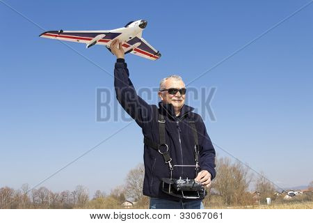 Happy senior RC modeller launching RC plane