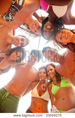 Group of friends at the beach smiling and hugging