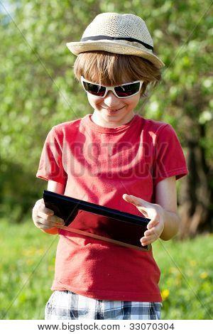 Joyful Boy Plays In The Tablet Pc
