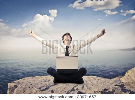 Triumphing young businessman sitting on a peak over the sea with a laptop on his knees