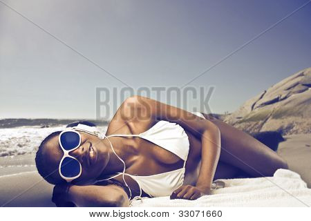 Smiling beautiful african woman lying on a beach