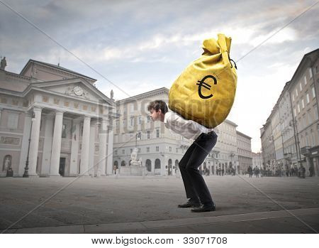 Young businessman carrying a money-bag on his shoulders on a town square