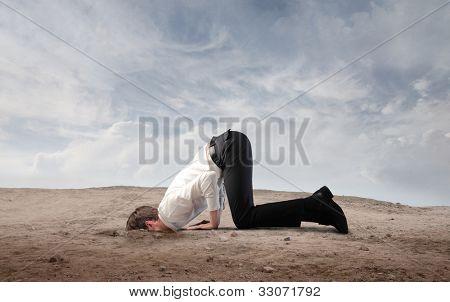 年轻的商人,把他的头埋在沙子里