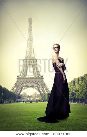 Beautiful elegant woman on a meadow with Eiffel Tower in the background