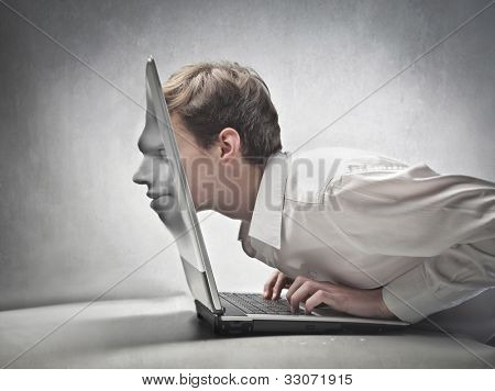 Young businessman passing his head through a laptop screen