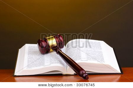 Richters Hammer und offenes Buch auf Holztisch auf braun Hintergrund