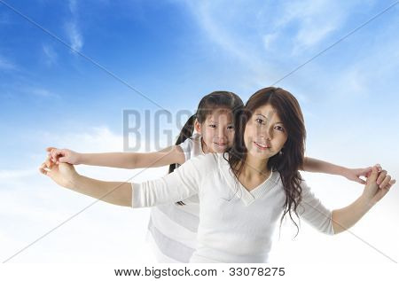 Happy Asian mother piggyback ride daughter over blue sky