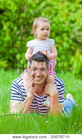 romantic scene of father hug child in green parl