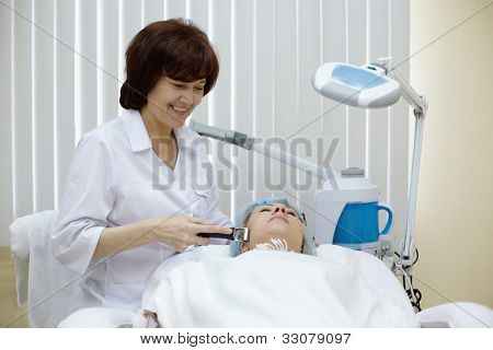 Smiling beautician in beauty salon processes face skin of the patient with the metal massage roller.
