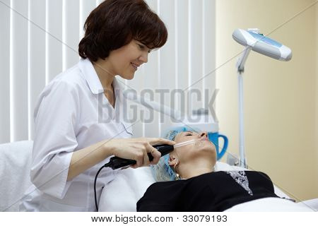 The employee of beauty salon processes face skin of the patient with the device of d'Arsonval.