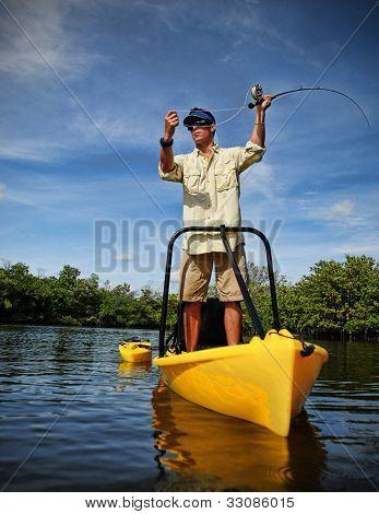 Man Fly Fishing In Kayak On Lake