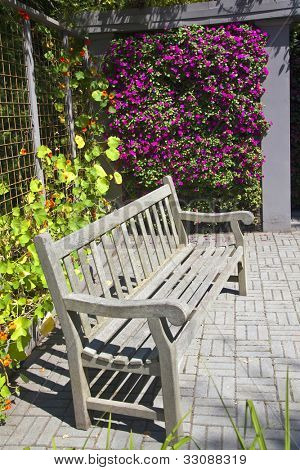 A wooden bench in a colorful garden niche with a profusion of annual flowers such as impatiens and nasturtiums.