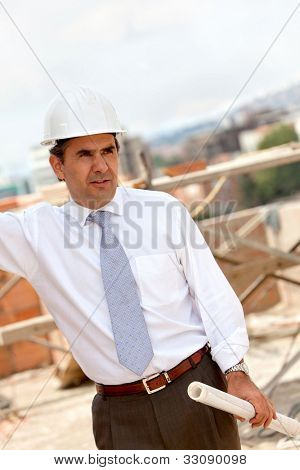 male engineer at a construction site holding blueprints