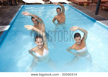 Smiling group doing aqua aerobics in swimming pool