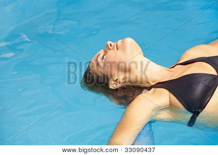 Attractive brunette woman floating in swimming pool