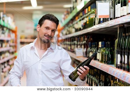 Portrait of smiling young man holding liquor bottle at supermarket