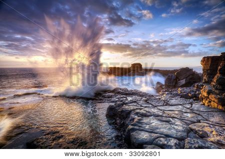 Scenic view of blowhole on rocky coastline with sunset cloudscape, Reunion Island, region of France.