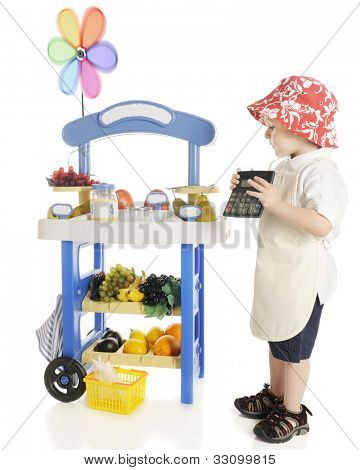 An adorable preschooler holding his calculator while looking over the produce on his fruit stand.  Signs left blank for your text.  On a white background.