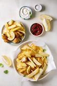 Classic British Fast Food Fish And Chips Served On White Paper In Plate With Lemons, Red And White S poster