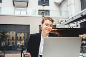 Young Smiling Business Woman Sitting At Coffee Shop On Veranda And Working On Laptop. Portrait Of Fe poster