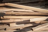Wooden Planks, Rods And Poles, Stockes In Piles And Stacks, Waiting To Be Used As Lumber By A Carpen poster