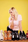 Attractive blonde woman standing looking down at a row of different shoes trying to make a choice