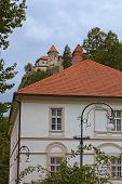 Big Two-storied Residential Building With Red Tile Roof. Famous Bled Castle At The Cliff In The Back poster
