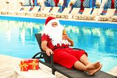 Authentic Santa Claus With Bottle Of Beer Near Pool At Resort poster