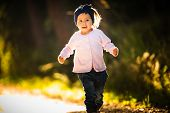 2 Years Old Baby Girl Running In Forest Towards Camera. With Happy Expression On Her Face poster