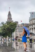China travel tourist woman walking in Shanghai city under the rain with umbrella. Asian woman walkin poster