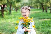 Little Smiling Blonde Girl With A Bouquet Of Yellow Flowers On A Background Of The Garden. A Child I poster