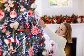 Child Decorating Christmas Tree. Kid On Xmas Eve. poster