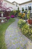 stock photo of molly  - Frontyard Cement Stone Paver Path on Green Lawn with Water Fountain Vertical - JPG