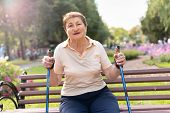 Old Woman Walks Nordic With Sticks In The Park On A Sunny Summer Day Outdoors poster