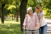 Caretaker Helping Elderly Woman With Walking Frame Outdoors poster