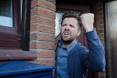 Angry Upset Young Male Neighbor With Fist In Air, Open Mouth Yelling. poster