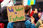 A Cardboard Sign Is Viewed Close-up Saying We Want A Future As A Crowd Of Environmental Campaigners  poster