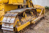Close-up Of Crawler Bulldozer Truck. Earthmoving Heavy Machinery. Yellow Crawler Machinery. Yellow T poster