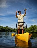 picture of fly rod  - Man casting fly fishing pole in yellow kayak on lake - JPG