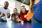 Young People Playing Table Tennis In Workplace, Having Fun. Friends In Casual Clothes Play Ping Pong poster