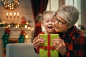 Merry Christmas and Happy Holidays! Cheerful grandma and her cute grand daughter girl exchanging gif poster