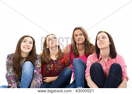 happy young women sitting together smiling and looking up and dreaming, over white background
