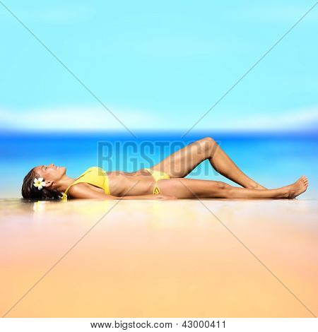 Beach vacation holiday woman in a bikini relaxing. Beautiful shapely woman in a bikini lying down in sand sunbathing in the summer sun on a pristine at an idyllic tropical paradise by turquoise ocean.